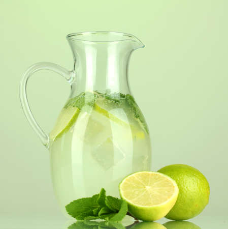 Lemonade in pitcher on green background photo