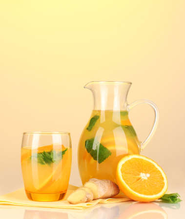 Orange lemonade in pitcher and glass on yellow background Stock Photo - 19988288