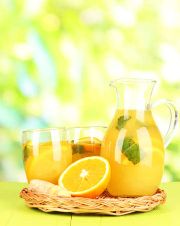 Orange lemonade in pitcher and glasses on wooden table on natural background photo