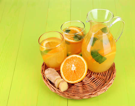 Orange lemonade in pitcher and glasses on wooden table close-up photo