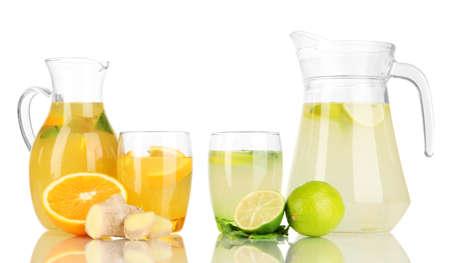 Orange and lemon lemonade in pitchers and glasses isolated on white photo