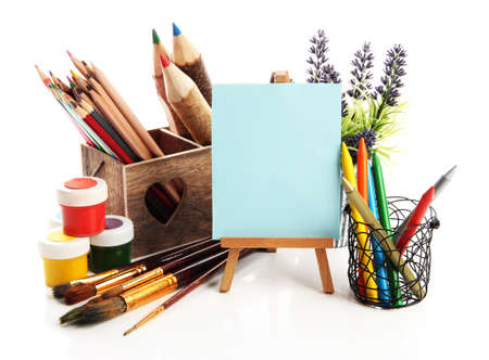 Pencils in wooden crate, paints, brushes and easel, isolated on white photo