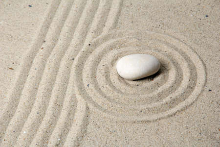 Zen garden with raked sand and round stone close up Stock Photo - 20012694