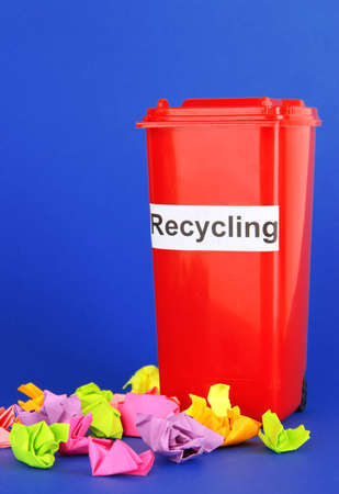 segregate: Recycling bin with papers on blue background