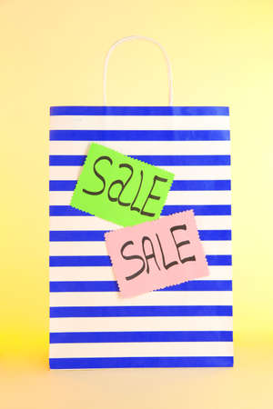 Striped bag on yellow background photo
