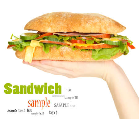 Fresh and tasty sandwich with ham and vegetables in hands isolated on white photo