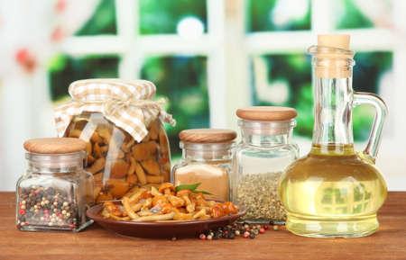 Zusammensetzung der köstlich marinierten Pilzen, Öl und Gewürze auf Holztisch auf hellem Hintergrund
