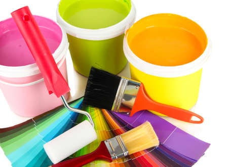Paint pots, paintbrushes and coloured swatches close up Stock Photo
