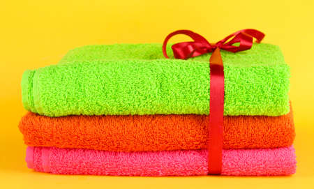 Towels tied with ribbon on yellow background photo