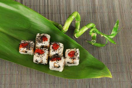Tasty Maki sushi - Roll on green leaf on mat photo