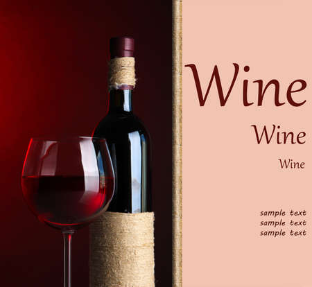 Bottle and glass with wine on dark red background photo