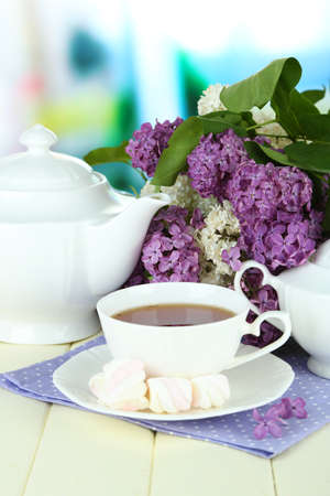 Composition with beautiful lilac flowers, tea service on wooden table on bright  background photo