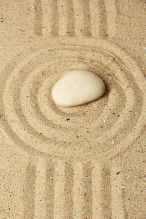 Zen garden with raked sand and round stone close up Stock Photo - 20126721