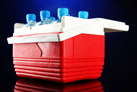 refrigerate: Traveling refrigerator with bottles of water and ice cubes, on blue background