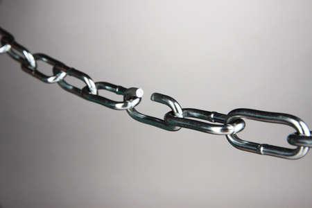 weakest: Broken chain on gray background