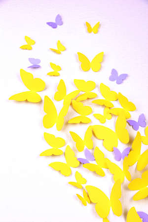 Paper yellow butterfly in form of heart on wall photo