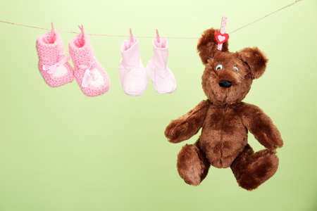 Baby booties hanging on clothesline, on color background photo