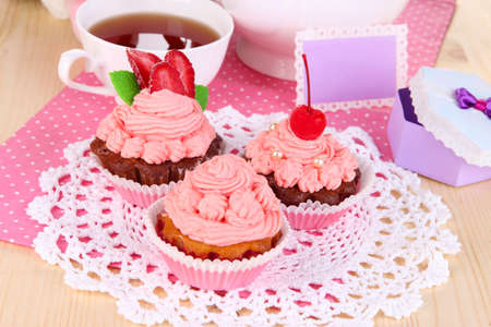 Beautiful strawberry cupcakes and flavored tea on dining table close-up photo