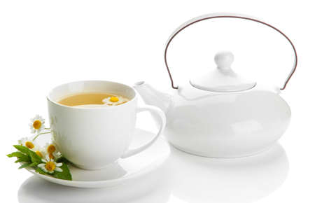 Cup and teapot of herbal tea with wild camomiles and mint, isolated on white photo