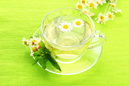 Cup of herbal tea with wild camomiles and mint, on green napkin photo