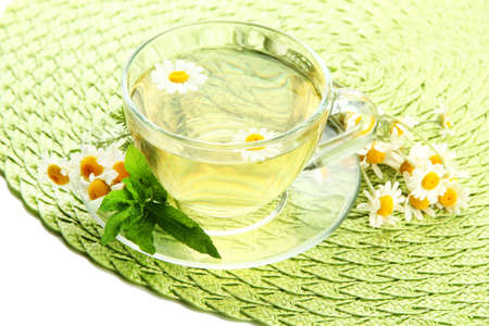 Cup of herbal tea with wild camomiles and mint, isolated on white photo
