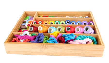 Colorful threads for needlework in wooden box isolated on white photo