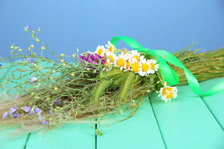 Bouquet of wild flowers and herbs, on wooden table on color background photo