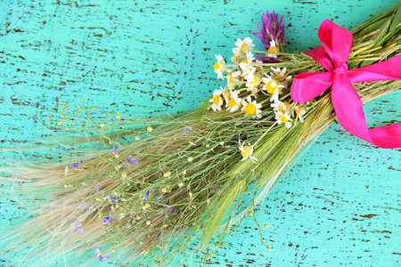 Bouquet of wild flowers and herbs, on color wooden background photo