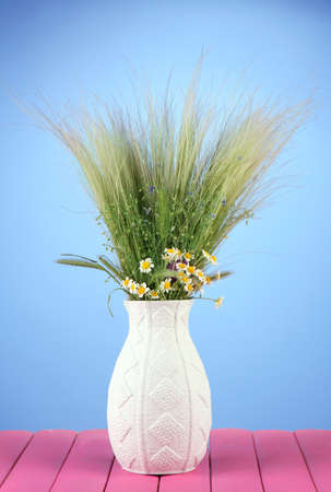 Bouquet of wild flowers and herbs, in vase, on wooden table on color background photo