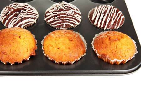Tasty muffin cakes in baking tray close up photo