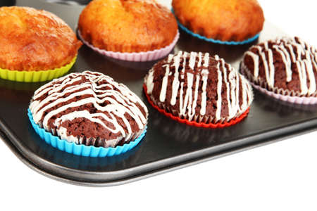 Tasty muffin cakes in baking tray isolated on white photo