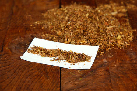 Tobacco and rolling paper, on wooden background photo