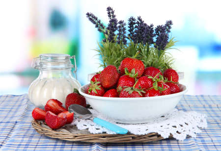 Strawberries in plate on wicker stand on table on wooden background photo