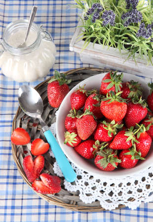 Strawberries in plate on wicker stand on napkin photo