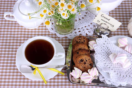 Table setting with chamomiles on checkered tablecloth photo