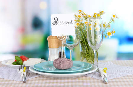 Table setting with chamomiles on checkered tablecloth on window background photo