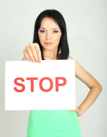 Girl showing stop sign on grey background Stock Photo - 20278964