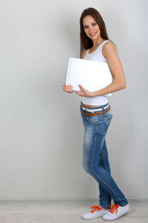 Beautiful young woman with laptop in room photo