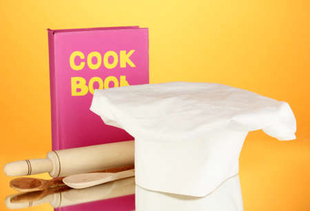 battledore: Chefs hat with battledore and cook book on orange background Stock Photo