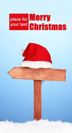 Wooden road sign with Santa hat on blue background photo