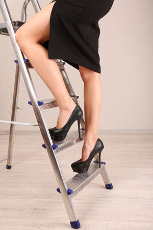 Woman climbing up ladder in office photo