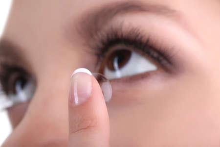 oči: Mladá žena uvedení kontaktní čočky v oku zblízka