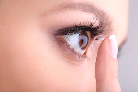 eye contact: Young woman putting contact lens in her eye close up Stock Photo