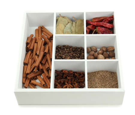 Assortment of aroma spices in white wooden box isolated on white photo