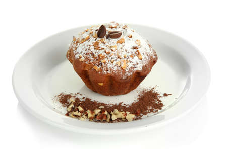 Tasty muffin cake with powdered sugar and cocoa on plate, isolated on white photo