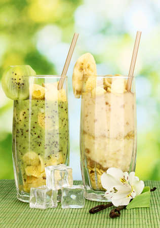 Delicious fruit smoothies on bright background photo