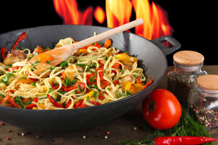 Noodles with vegetables on wok on fire background photo
