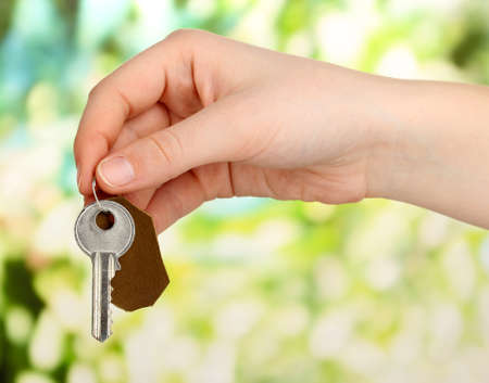 bibelot: Key with leather trinket in hand on bright background