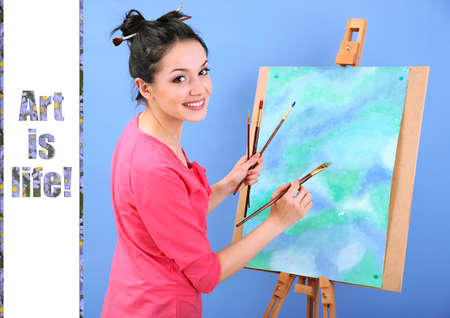 Beautiful young woman painter at work, on color background photo