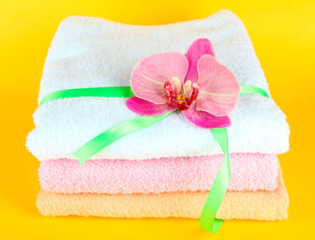 orange washcloth: Towels tied with ribbon on yellow background